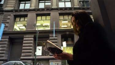 A woman reads a book in front of the Flinders Lane building in 2002, before it became a library.