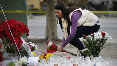 Jennifer Caballero places flowers at a makeshift memorial to the victims of Wednesday's shooting rampage in San Bernardino.