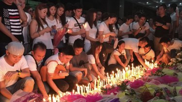 Mourners light candles and lay flowers in front of a memorial outside the casino.