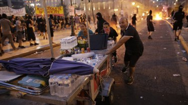 Food vendors rush to clear the area in Syntagma Square during police clashes with protesters in Athens on Wednesday.
