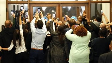People rush the doors of the jury assembly room as former president Barack Obama departs after being dismissed from jury duty in the Daley Centrer on Wednesday.