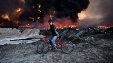A boy pauses on his bike as he passes an oil field that was set on fire by retreating IS fighters ahead of the Mosul offensive in Qayyarah, Iraq.