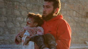 Pulled from the wreckage: A man carries a Syrian child to safety following airstrikes on residential areas of Aleppo, Syria in November.