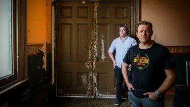 Luke  Hikakari and Matt Kunkel with a door that's seen better days.