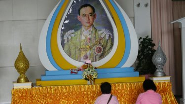 Thais pray in front of a portrait of King Bhumibol Adulyadej in Bangkok.