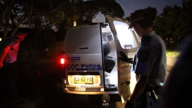 Terrorism arrests: A man is put into a police vehicle in Marsfield.
