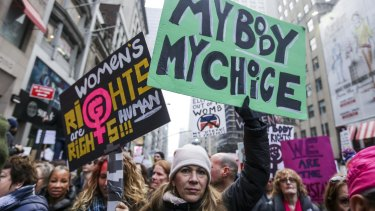 Demonstrators hold signs while marching towards Trump Tower in New York in January, following Trump's inauguration.