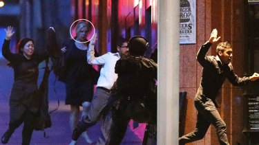 Pregnant Sydney siege survivor Julie Taylor (circled) runs with other hostages from the Lindt cafe in Martin Place.