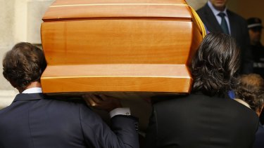 Family members carry in her coffin.