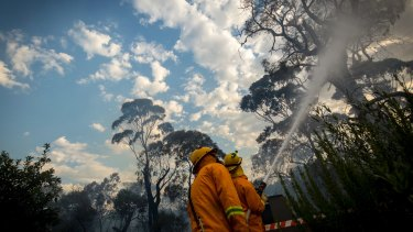 CFA members fight a fire threatening homes in Valley Road Skye.