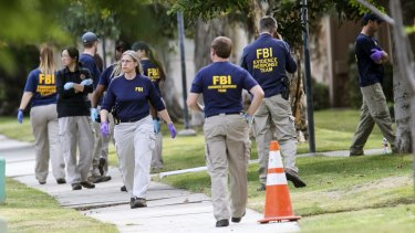 FBI agents search outside a home in connection to the shootings in San Bernardino.