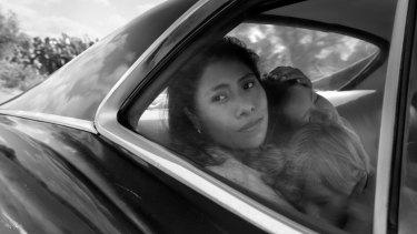 Yalitza Aparicio as Cleo, Marco Graf as Pepe, and Daniela Demesa as Sofi in Alfonso Cuaron's neorealist drama <i>Roma</i>.