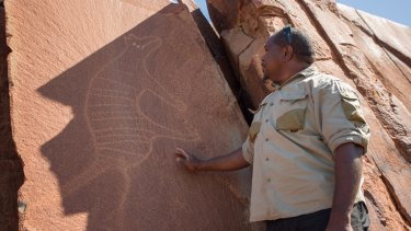 Senior cultural ranger at Murujuga National Park, Dallas Fredericks, stands next to a rock carving of a thylacine (Tasmanian tiger).