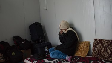 M weeps at parting from relatives en route to a resettlement program in Germany, at a camp near Dohuk, Iraq.