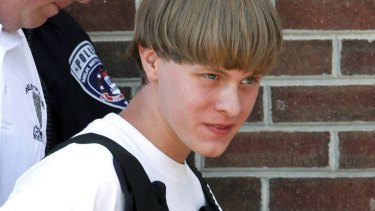 Police lead suspected shooter Dylann Roof into the courthouse.