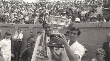 Ken Rosewall holds the cup after beating Mal Anderson, left, at Kooyong.