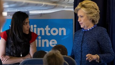 Hillary Clinton speaks with Huma Abedin aboard her campaign plane to Iowa on Friday.