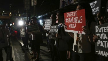 Filipino students shout slogans during a protest on Monday against Duterte's closure of independent news website Rappler.