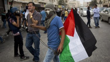 A Palestinian holds a sling during clashes with Israeli troops at Qalandia checkpoint in the occupied West Bank.