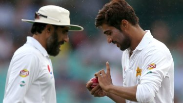 Long day: Pakistan's Mohammad Amir, right, polishes the ball as his captain Pakistan's Misbah-ul-Haq walks past.