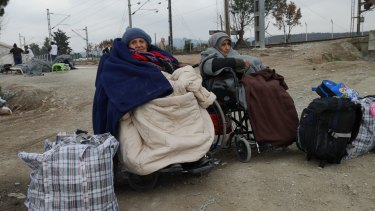 Two women in wheelchairs wait for the border to Macedonia to open.