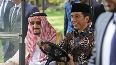 Saudi King Salman, left, rides on a golf cart with Indonesian President Joko Widodo.