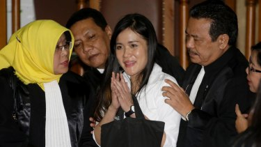 Jessica Kumala Wongso, centre, flashes a smile as she is surrounded by her lawyers after her jail sentence at a courtroom of Central Jakarta District Court.