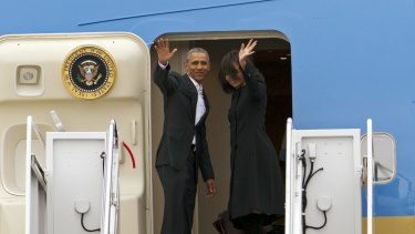President Barack Obama, accompanied by first lady Michelle Obama, waves while boarding Air Force One before their departure  at Andrews Air Force Base, Maryland.