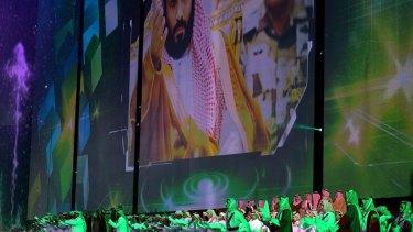 Saudi men perform under a giant screen showing an image of Saudi Crown Prince Mohammed Bin Salman during National Day ceremonies in Riyadh, Saudi Arabia.