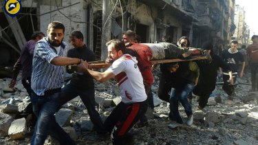 Syrians carry a victim after air strikes by government helicopters on the Aleppo neighbourhood of Mashhad on Tuesday.