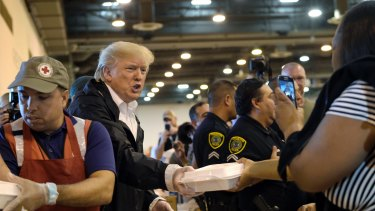 President Donald Trump passes out food and meets people affected by Hurricane Harvey during a visit to the NRG Center in Houston.