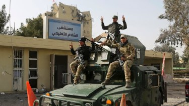 Iraqi security forces flash V signs for victory outside al-Salam hospital in Mosul, Iraq, in early January.
