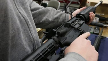A man holds a semi-automatic assault rifle at the Rocky Mountain Gun Show in Sandy, Utah.