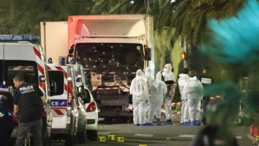 French police forces and forensic officers stand next to a truck that ran into a crowd in Nice.