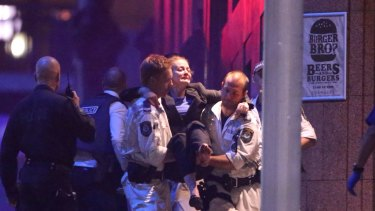 A hostage is carried out of Martin Place to a waiting ambulance in the early hours of Tuesday morning.