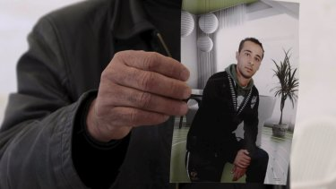 The cousin of Yassine al-Abidi, who gunned down 20 foreign tourists at Tunisia's Bardo museum, shows a photo of Yassine during an interview in Tunis.