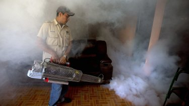 A worker from the Ministry of Health sprays insecticide inside a home to eradicate the mosquitoes responsible for spreading the Zika virus in Guatemala City.