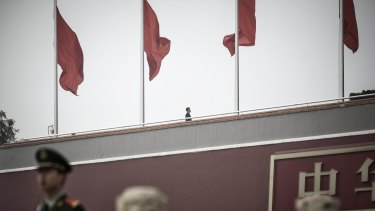 A paramilitary police officer and a security official stand guard near red flags at Tiananmen Gate in Beijing, China.