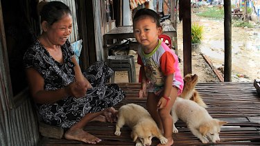 A woman plays with a child in Khmounh, Cambodia. Poverty has compelled many women to seek income as surrogate mothers or through selling their breast milk.