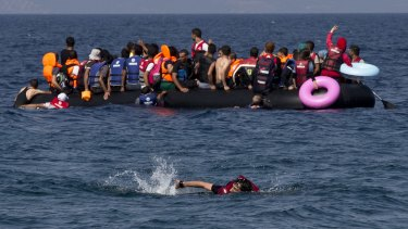 A Syrian man swims in front of a dinghy full of refugees off the Greek island of Lesbos.