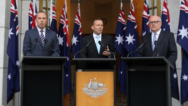 Immigration Minister Peter Dutton, Prime Minister Tony Abbott and Attorney-General Senator George Brandis stand in front of ten flags at a press conference the day after Mallah appeared on <i>Q&A</i>.