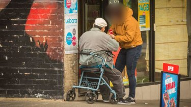 A shopkeeper appears to sell illegally imported cigarettes to a man at a Melbourne milk bar.