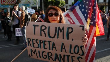 """A woman holds a sign that reads in Spanish """"Trump, respect migrants"""" in Mexico on the day of his inauguration."""