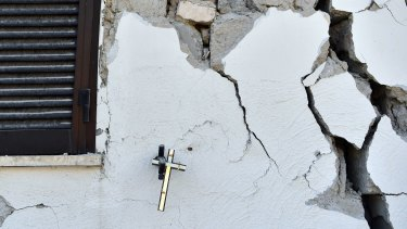A crucifix hangs on the wall of a damaged house in Amatrice, Italy.