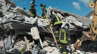 Firefighters search through debris in Amatrice.