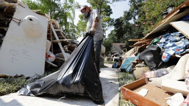 Volunteer Mark Staerkel removes debris from a home destroyed by floodwaters in the aftermath of Hurricane Harvey.