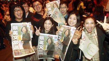 Supporters of the Democratic Progressive Party's Tsai Ing-wen display newspaper headlines featuring the newly elected president.