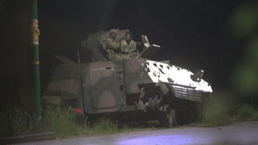 Armed Zimbabwean soldiers sit on top of a military tank in Harare, Zimbabwe early on Wednesday morning
