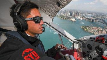 Pilot Daniel Johnson flies over Sydney Harbour.