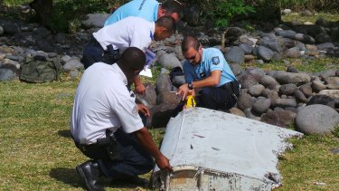 French police inspect a large piece of plane debris that was found on the beach in Saint-Andre, on Reunion Island, in July.